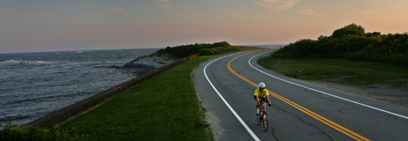 Road cycling, 2010 bike tour - two bicylists silhouetted against the ocean